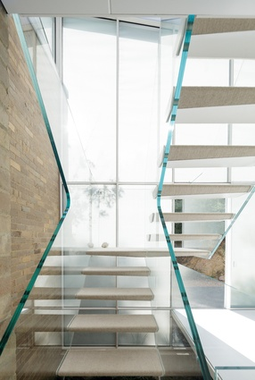 The uniquely sculptural form of the toughened glass stair has become a focal point in the space.