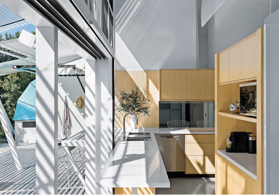 The arrangement of sliding glass doors at ground level and aluminium roller doors above optimizes air flow and moderates the home's internal temperature.