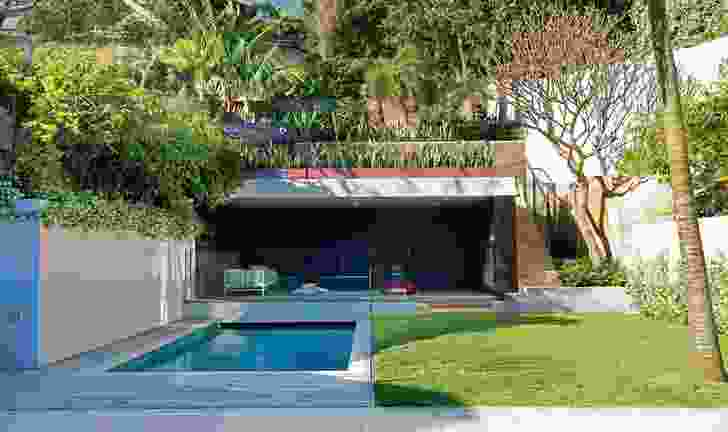 An enclosed courtyard with a pool connects the house to a lush garden at the rear.