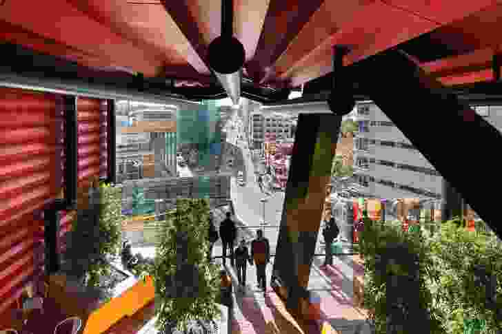 """The view from a portal space towards the kink in Swanston Street, the Hardrock indoor rock-climbing centre, Design Hub and the """"federation freestyle"""" of the Melbourne City Baths"""