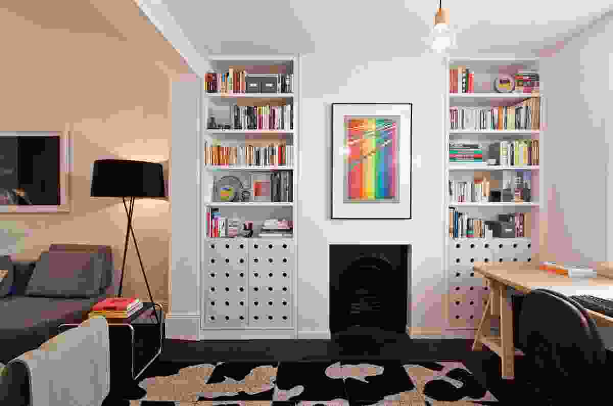 The old mantelpiece was removed and fireplace flanked with floor-to-ceiling bookcases. Artwork: Michael Smither.
