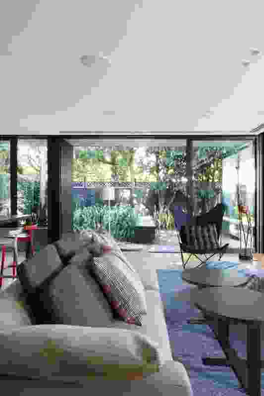 The rear living spaces open out onto a lush garden and a series of plinths surrounding a fire pit.