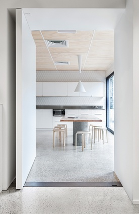 The communal kitchen on the upper level features an enormous dining table with a maple tabletop on concrete pipe legs.
