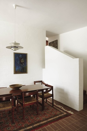 The long dining table sits under a Louis Poulsen lamp. The design of the short stair is reminiscent of the treatment of the external white wall at the front of the house.