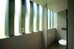 Panes of translucent glass between the stainless steel panels fill the bathrooms with natural light.