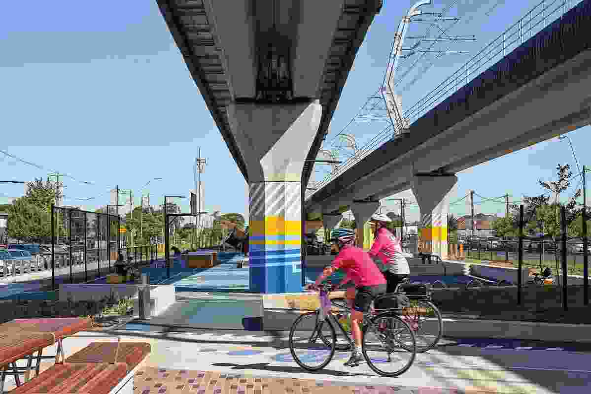 Shared cycling-pedestrian paths and picnic areas improve connectivity along the rail corridor.