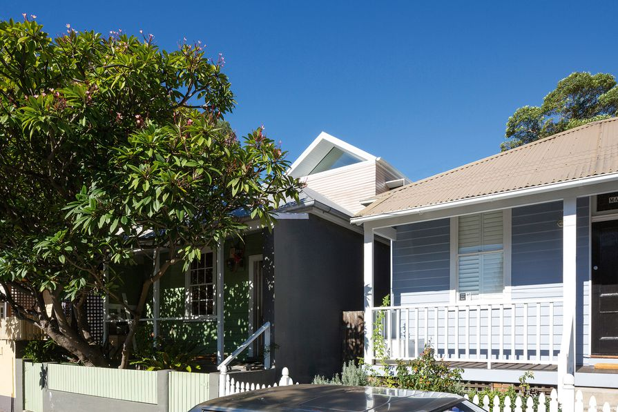 The gable-roofed addition floats above the modest single-storey brick and green weatherboard cottage.