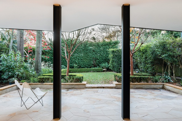 The view into the rear garden at V House (2018) in Mosman is framed by the upper-level soffit's angled edge and by geometric-cut stone underfoot.