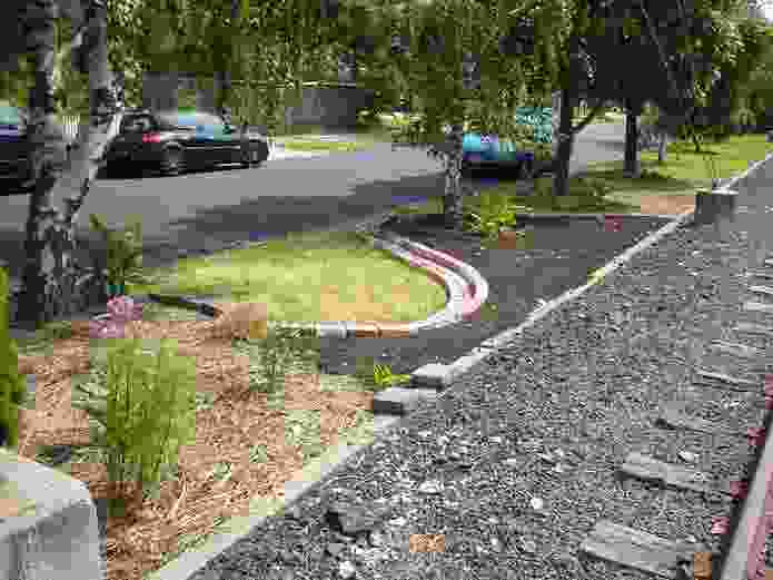 The garden in about 2008, soon after work began on it, showing legacy trees and weedy lawn, with new soil in edged beds and some early plantings.