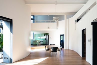 The apartment's main living space bends with the arc of the crescent-shaped roof terrace.