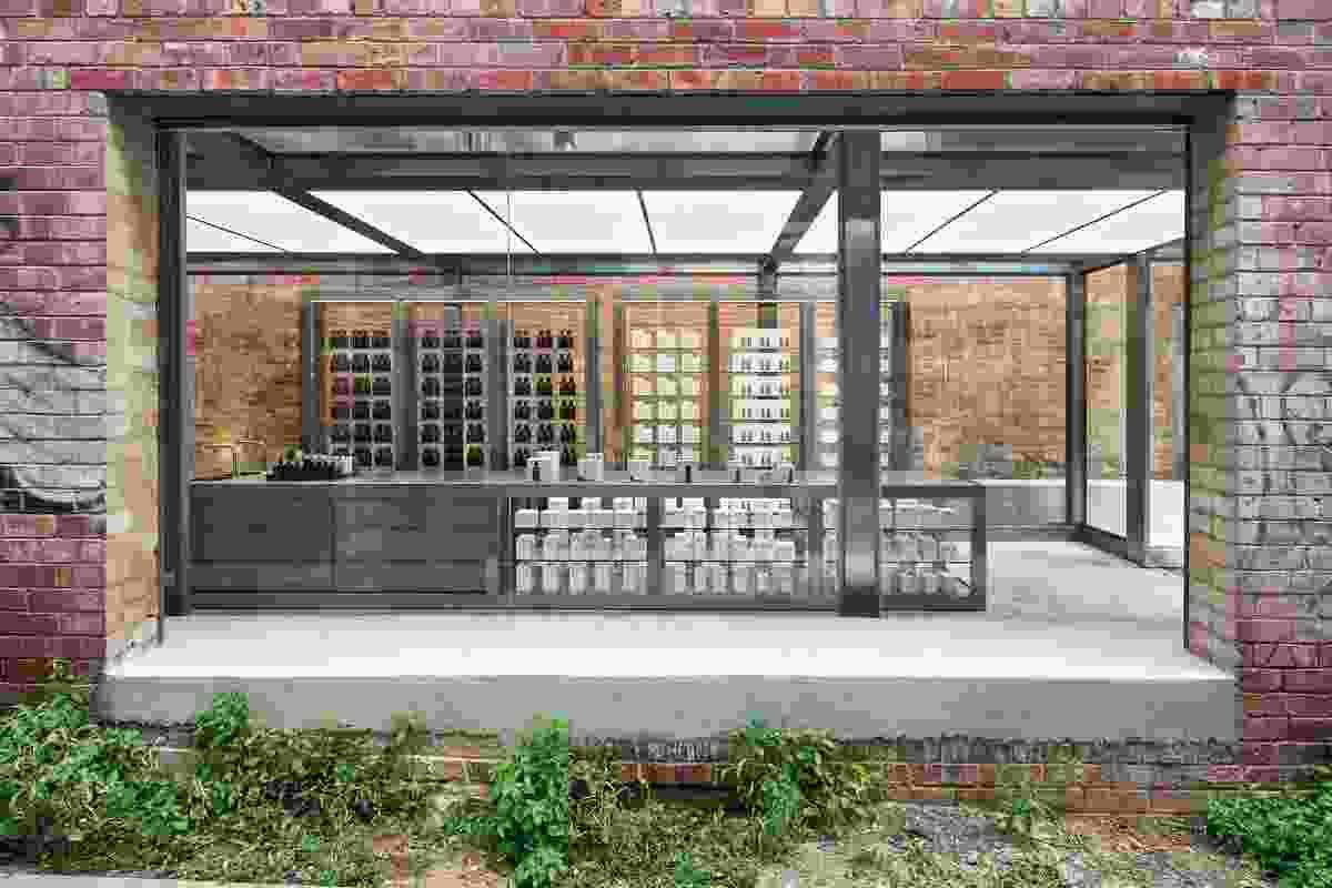 通往露台住宅后面的商店入口的旅程,让人们可以通过旧砖墙上的开口瞥见零售空间。