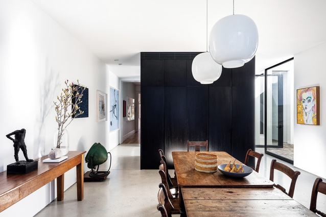 A large section of black joinery separates the dining and living areas from the kitchen.