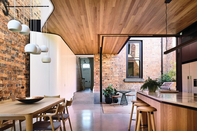 A void opening up to a skylight above the second floor scatters light across the rugged surface of the brick wall.