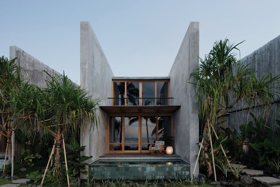 The hotel's two-storey accommodation villas are positioned radially across the site, with chasms between them framing views of the mountains in one direction and the sea in the other.
