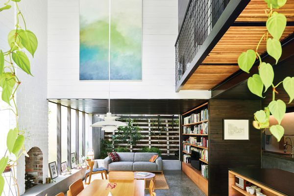 A double-height volume rises over the dining table, filling the depths of the lower level with northern light. Artwork (L-R): Jordy Hewitt; Laura Patterson.