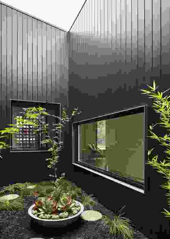A small garden near the entry portico allows natural light to filter into the bedrooms and study.