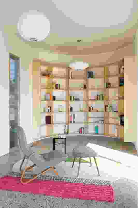"""The semicircular end of the room is wrapped in bookshelves, designed to create a """"wallpaper of books"""" with the clients' extensive collection."""