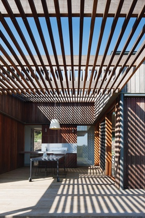 A sheltered outdoor kitchen is scooped out of the rectangular form of the house and roofed by a tracery of parallel battens.