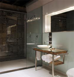 Crisp, cool bathrooms are inserted into the heritage fabric of the hotel rooms.