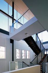 The foyer with the new centrepiece stair. The massive steel frame supporting the roof canopy is strutted to the warehouse wall beyond.