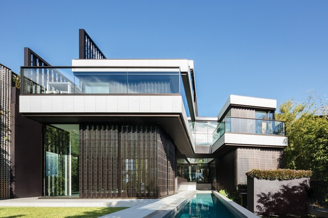 At the rear, the house splits into two wings, bounded by a bridge that joins the front edges of the two parts over a lap pool.