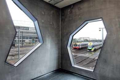 Irregularly shaped windows frame views of Melbourne's rail yards and city skyline.