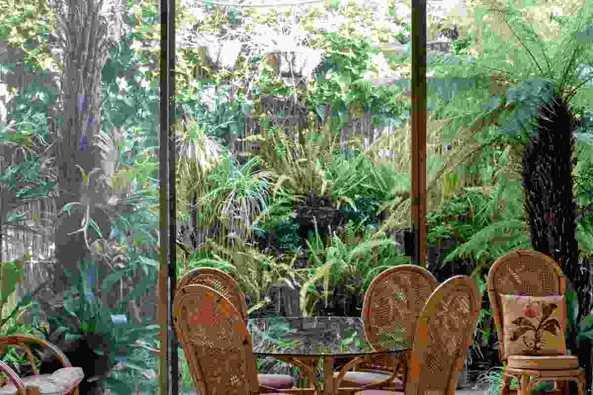Floor-to-ceiling glass openings connect to the garden.