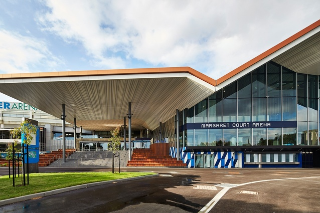 The main entrance to the arena is located to the north-east, its large overhanging roof framing the arrival stairs that double as tiered seating.