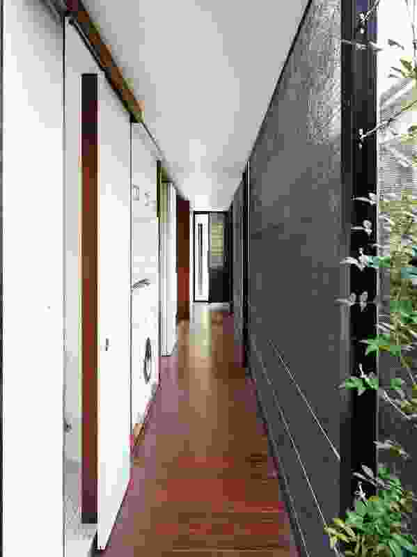 A corridor separated from the elements only by shadecloth serves as the house's primary circulation.