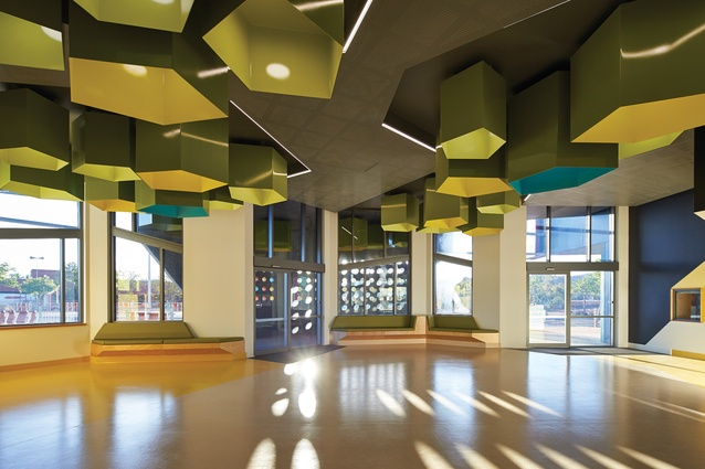The layout offers patients a choice to wait outside under shelter or inside the central waiting area, which features pentagonal extrusions in hues of green and yellow.