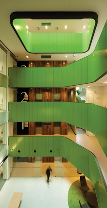 The foyer stretches through the building as an atrium, with the thick green horizontal elements restoring a sense of human scale.