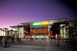 """Suncorp Stadium – known as the """"Cauldron"""" – seen across the South Plaza. The low hovering roof was designed to minimize light and sound spill."""