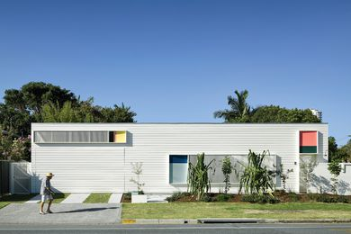 The entry facade is a playful composition of blocks of colour and battened screens on a white background.
