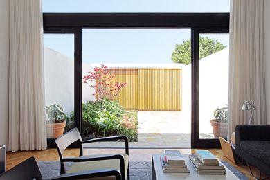 Full-height glazing in the living area opens onto sandstone paving.