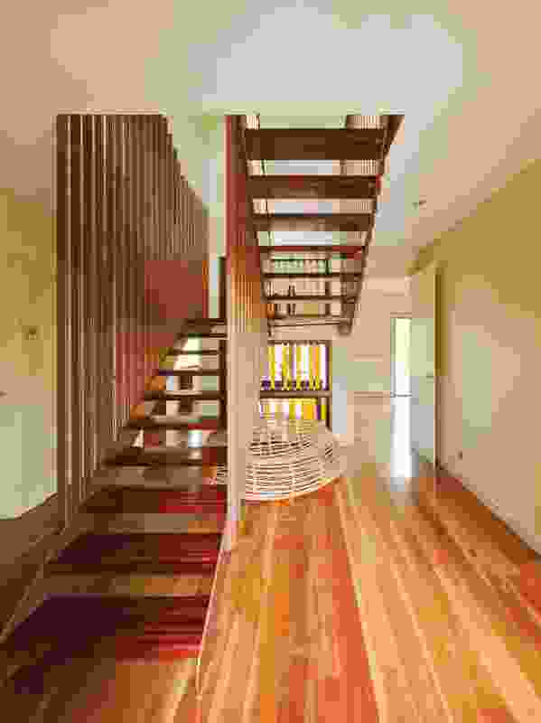 A hand-crafted staircase rises from the spotted gum floorboards.