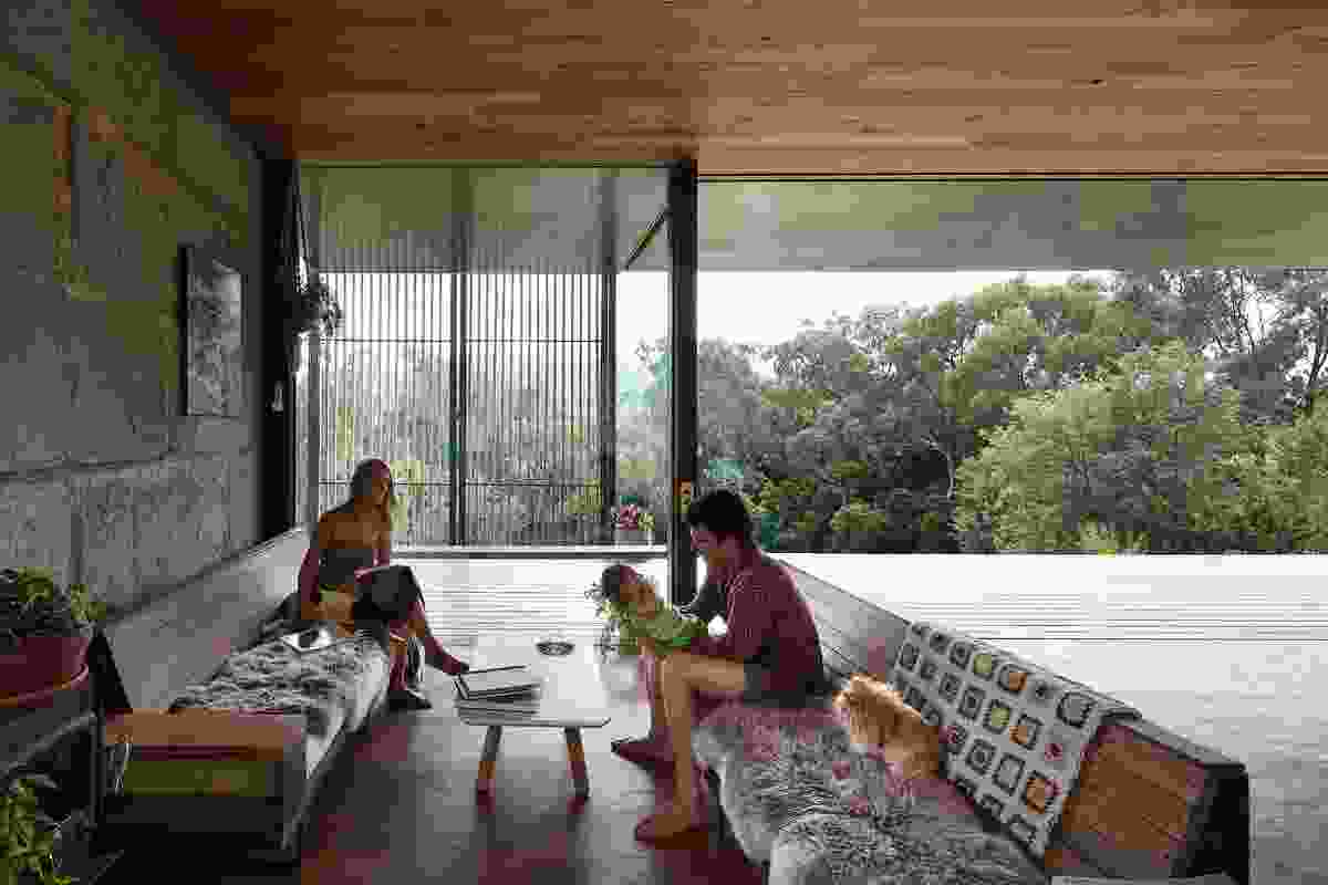 The main living space runs along the verandah, merging it through the use of a giant glass sliding wall.