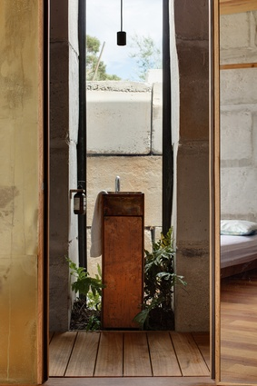 On the more private side of the house, the compact bathroom buries itself into the wall.