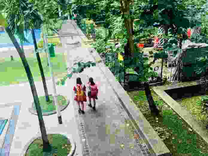 Children in Singapore, walking to school through the neighbourhood community gardens.