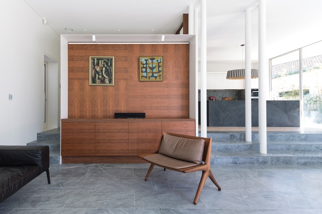 Three main cabinetry units (including this one in the living room) are framed in white metal. Artwork: Leonard French (left); John Coburn (right).