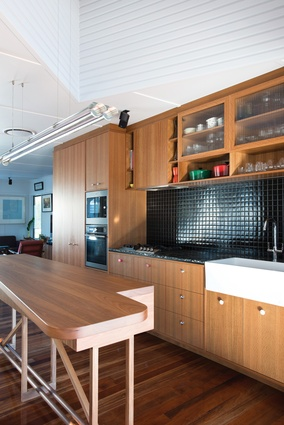 The kitchen features a custom-designed island bench and pendant light above.