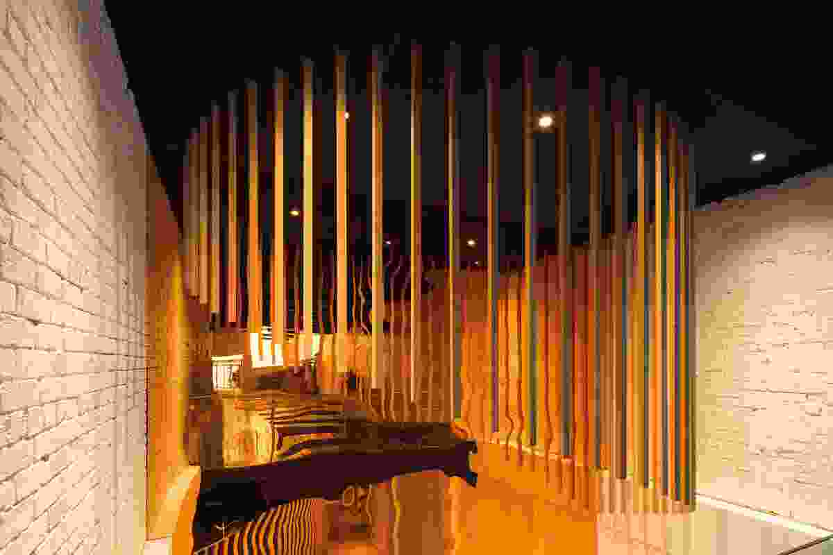 Representative of the sun, an effervescent installation composed of hanging timber battens is arranged in a semicircle.