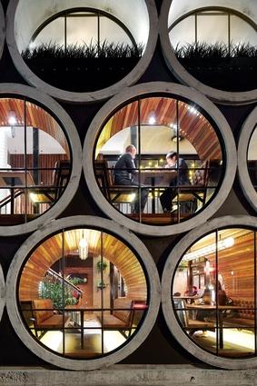 Concrete pipes encapsulate booths along the facade.