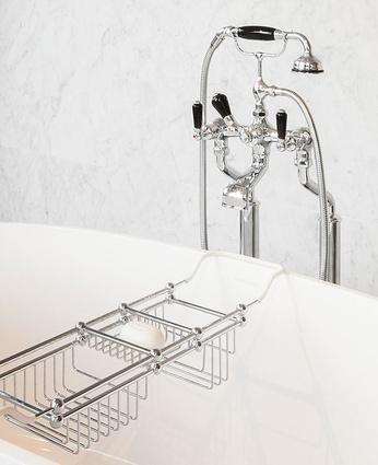 Freestanding bath filler with handshower and black porcelain levers.