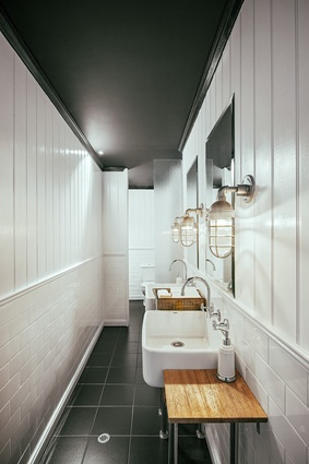 The bathrooms feature expanses of white timber panelling.