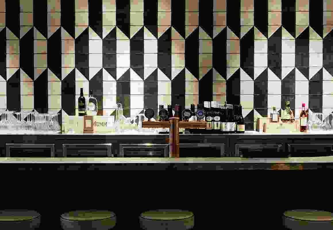 The bar features a wall of custom-made cream and black geometric tiles.