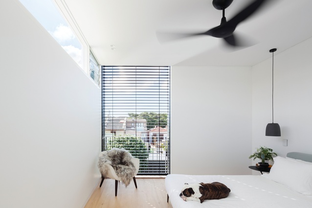 A large, full-height window in the main bedroom has a view into the garden and across neighbouring rooftops.