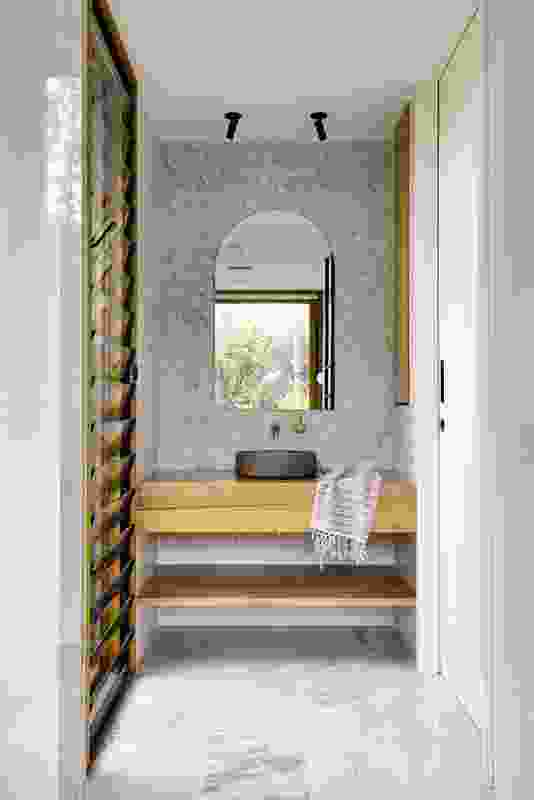 Louvre windows and a strategically placed mirror blur the boundary between the bathroom and abundant garden.