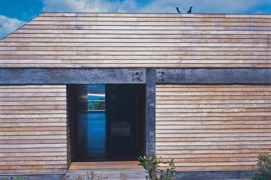 The timber-clad home frames spectacular views of Merimbula.
