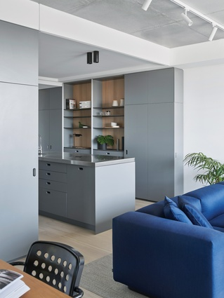 The spacious kitchen features cool monochromatic joinery, oak veneer and stainless steel.