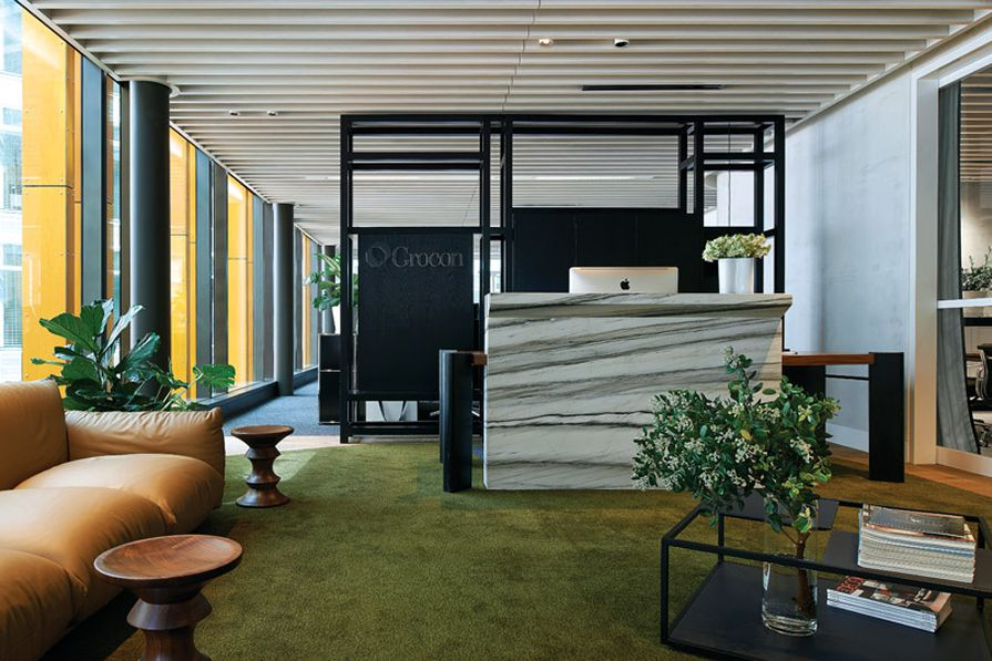 The custom-designed joinery behind the reception desk divides the lounge area from workspaces.